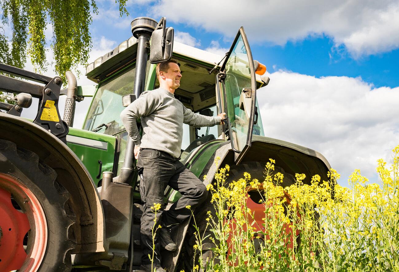 Landwirt steht an seinem Traktor und schaut übers Land